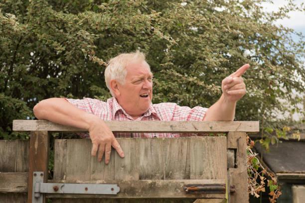 mature man shouting and pointing over a fence - vizinho imagens e fotografias de stock