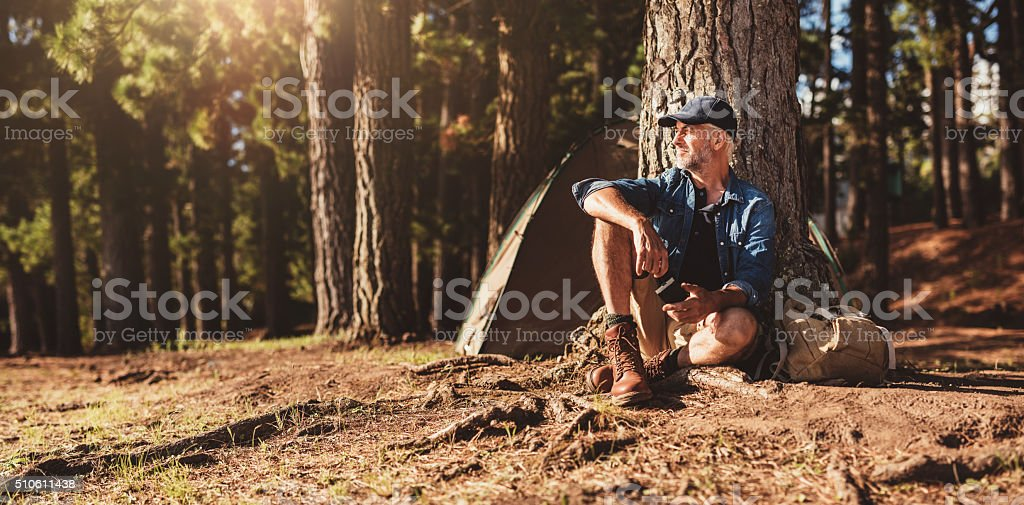Mature man sitting at a campsite stock photo