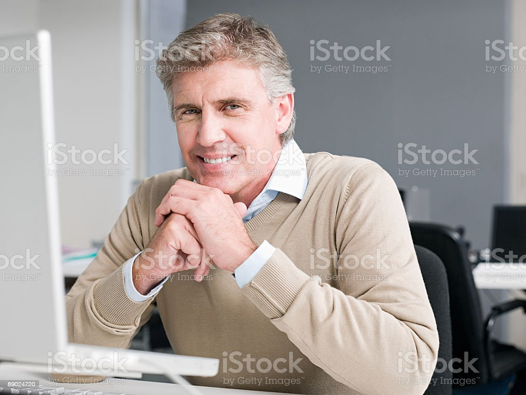 Mature man sitting at a laptop computer royalty-free stock photo