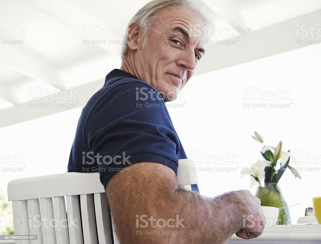 Mature man sitting at breakfast table, portrait, low angle view royalty-free 스톡 사진
