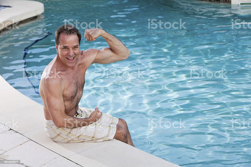 Mature man sitting at edge of pool stock photo