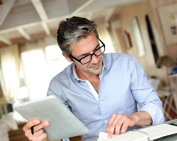 Reifer Mann sitzt zu Hause und Arbeiten mit tablet – Foto