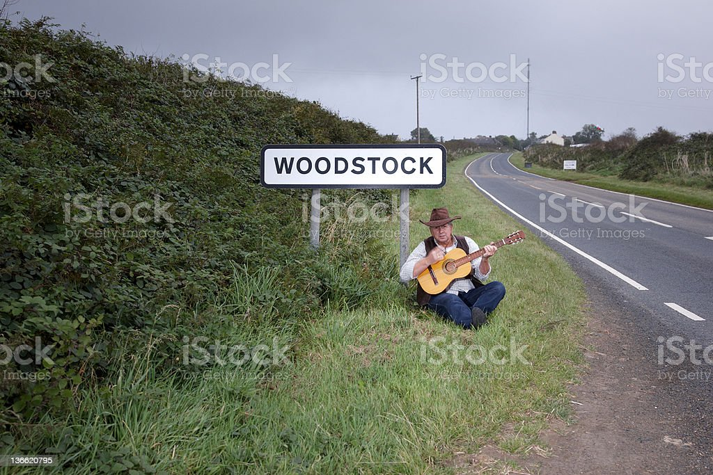 Mature man sitting at roadside with guitar royalty-free stock photo