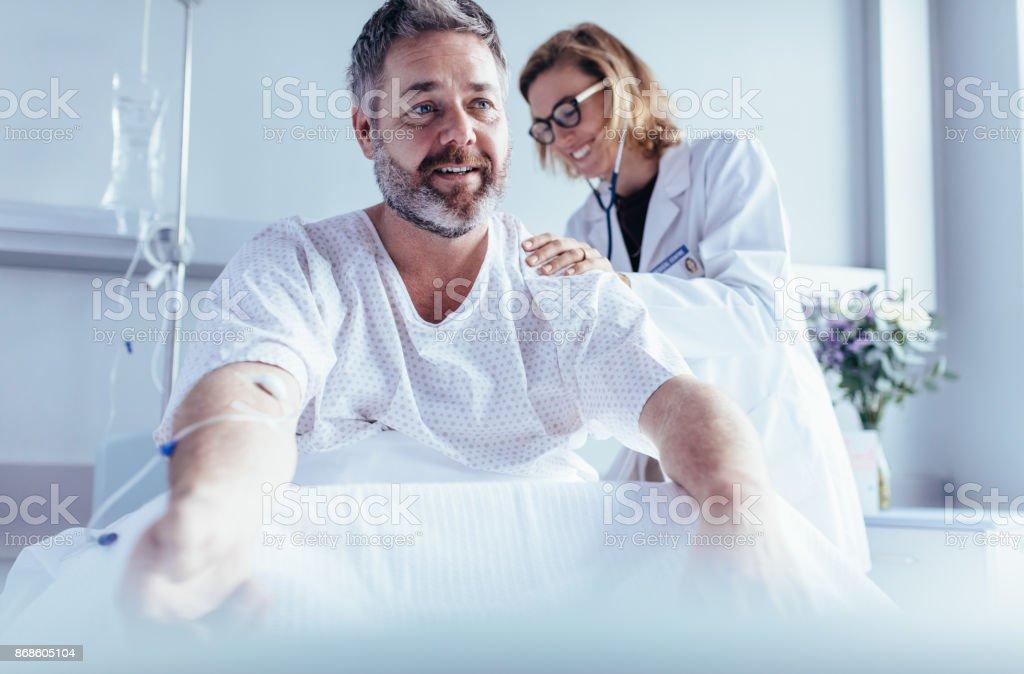 Reifer Mann sitzen im Krankenhausbett und Arzt Checkup zu tun. - Lizenzfrei Arbeiten Stock-Foto