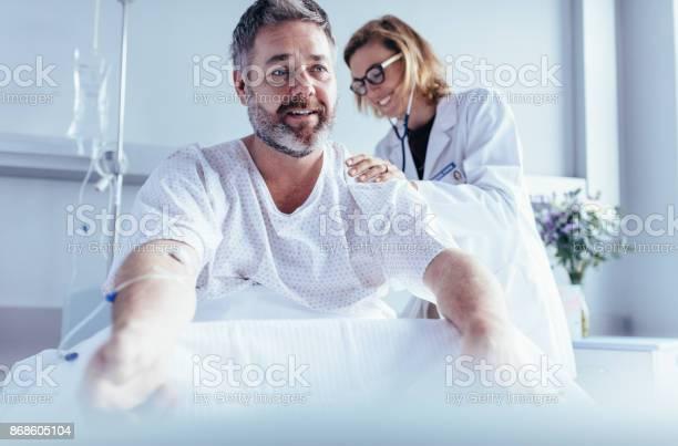 Reifer Mann Sitzen Im Krankenhausbett Und Arzt Checkup Zu Tun Stockfoto und mehr Bilder von Arbeiten