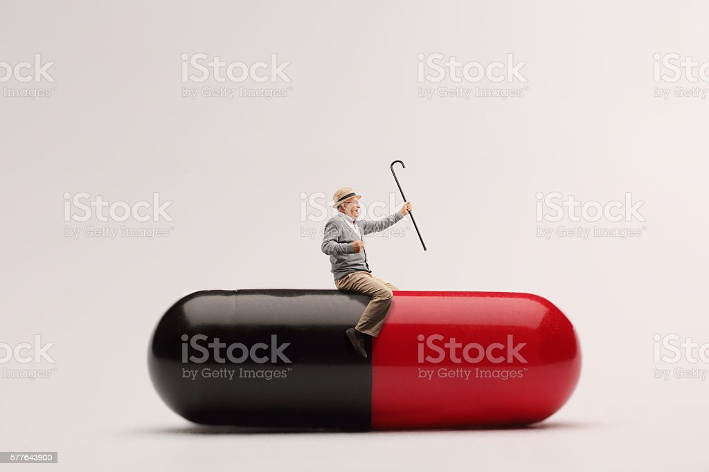 Mature man sitting on a giant pill stock photo