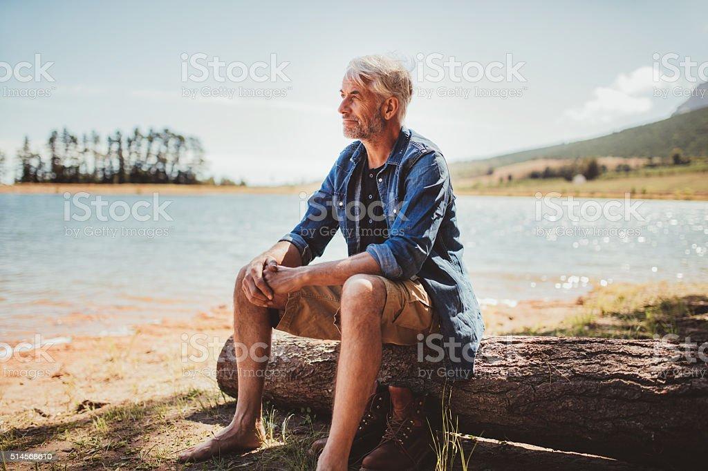Mature man sitting on a log near lake stock photo