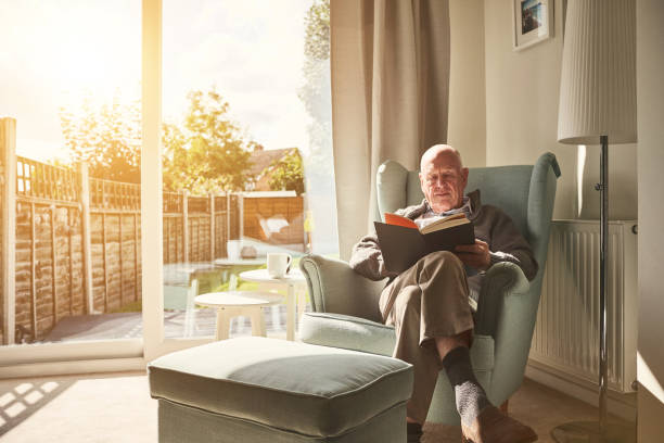 mature man sitting on arm chair and reading a book - senior home stock photos and pictures