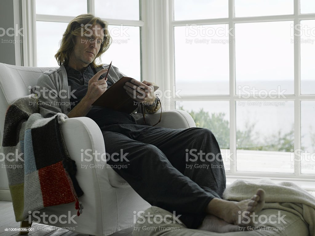 Mature man sitting on arm chair, reading diary royalty-free stock photo