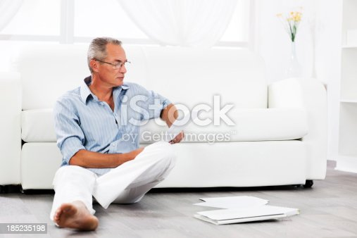 530281733istockphoto Mature man sitting on floor and looking at documents. 185235198