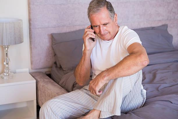 älterer mann sitzt auf seinem bett an - nachttischleuchte touch stock-fotos und bilder