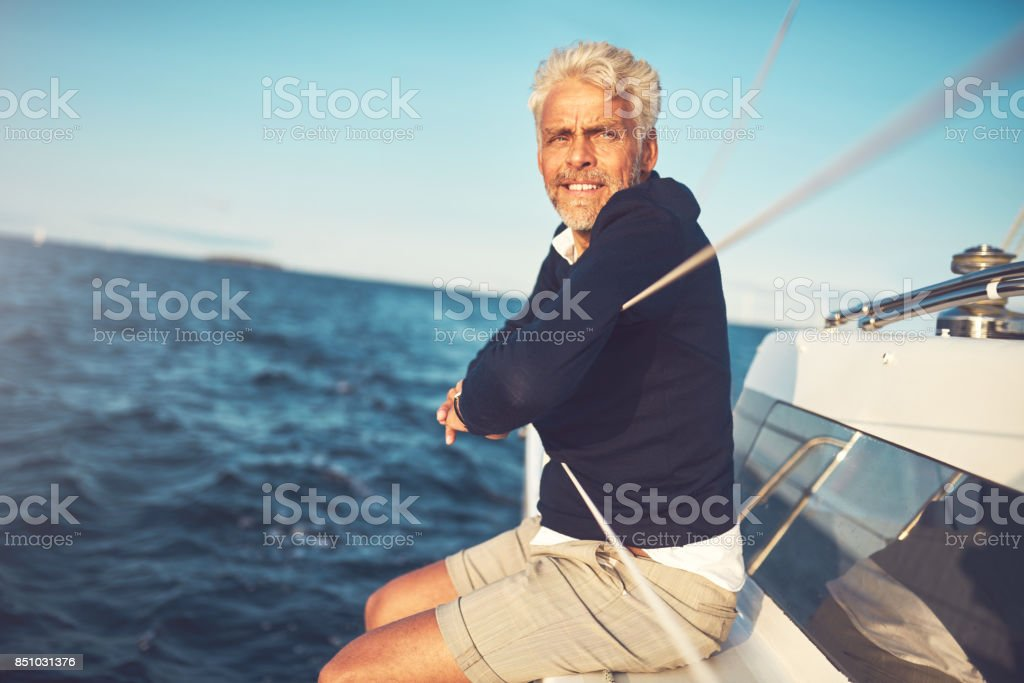 Mature man sitting on his sailboat looking at the ocean stock photo