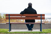 Rear view of mature man sitting on park bench overlooking river.