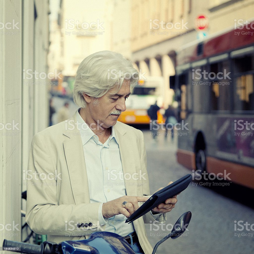Mature man sitting on scooter with digital tablet royalty-free stock photo