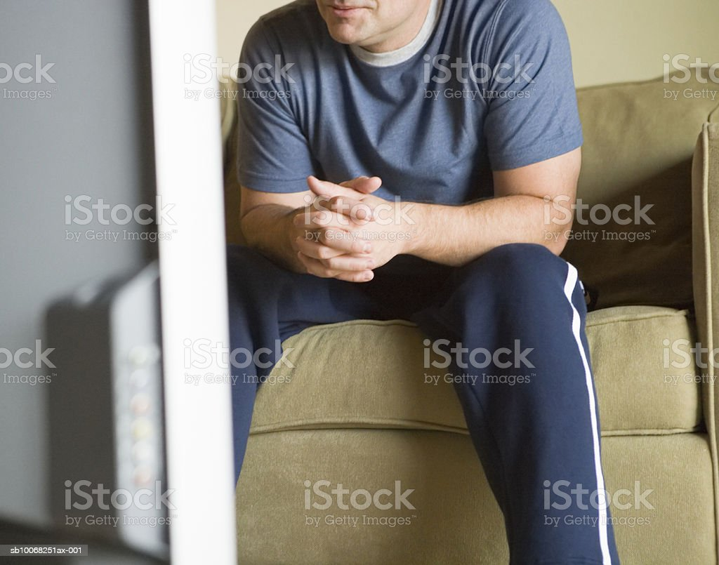 Mature man sitting on sofa, watching tv, mid section royalty-free stock photo