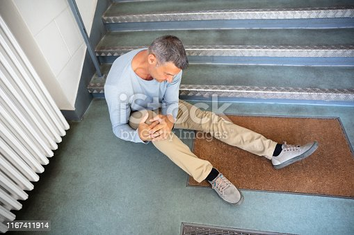 Mature Man Sitting On Staircase After Slip And Fall Accident
