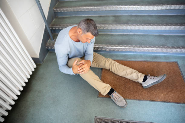 Mature Man Sitting On Staircase Mature Man Sitting On Staircase After Slip And Fall Accident falling stock pictures, royalty-free photos & images