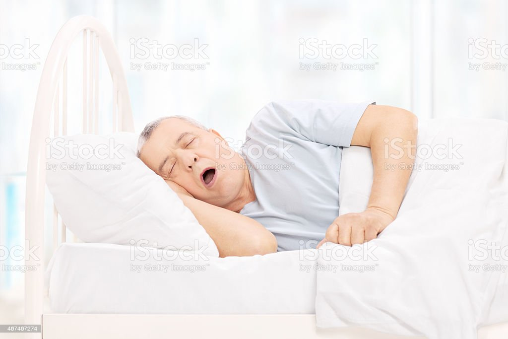 Mature man sleeping in a comfortable bed stock photo