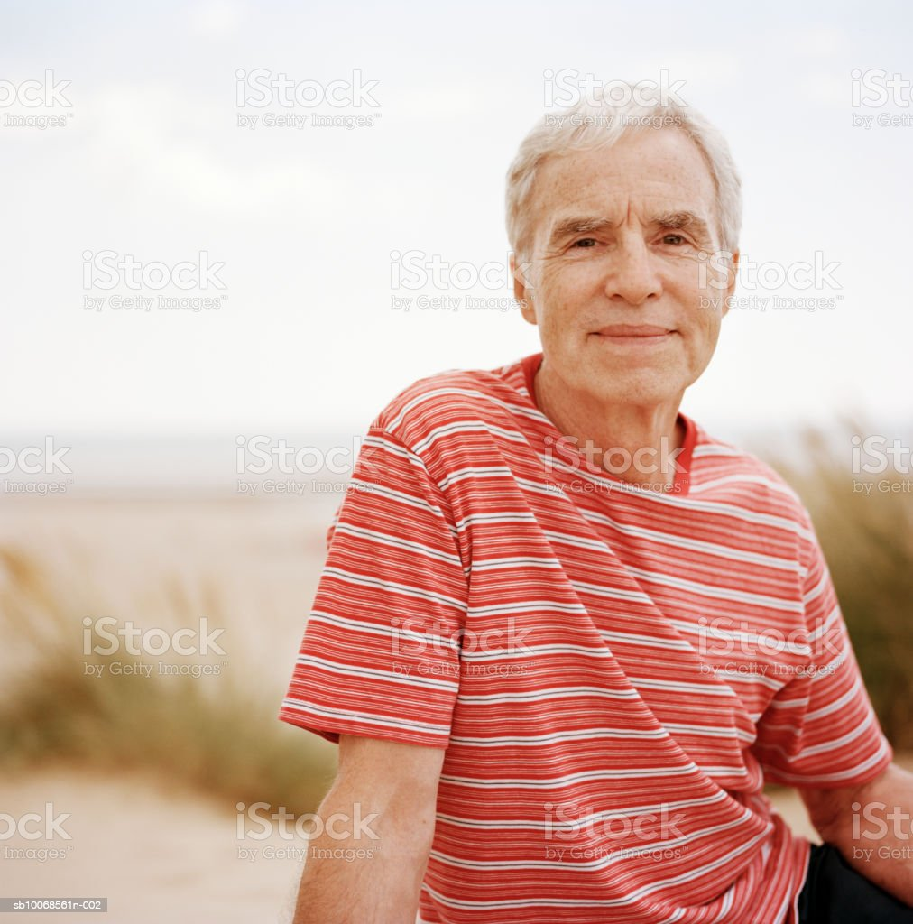 Mature man smiling on beach, portrait foto de stock royalty-free