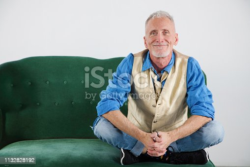 Mature man smiling portrait in hip clothes portrait on vintage couch, smiling kindly at the camera..
