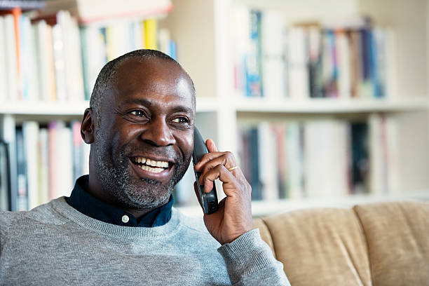 Mature Man smiling while on a telephone