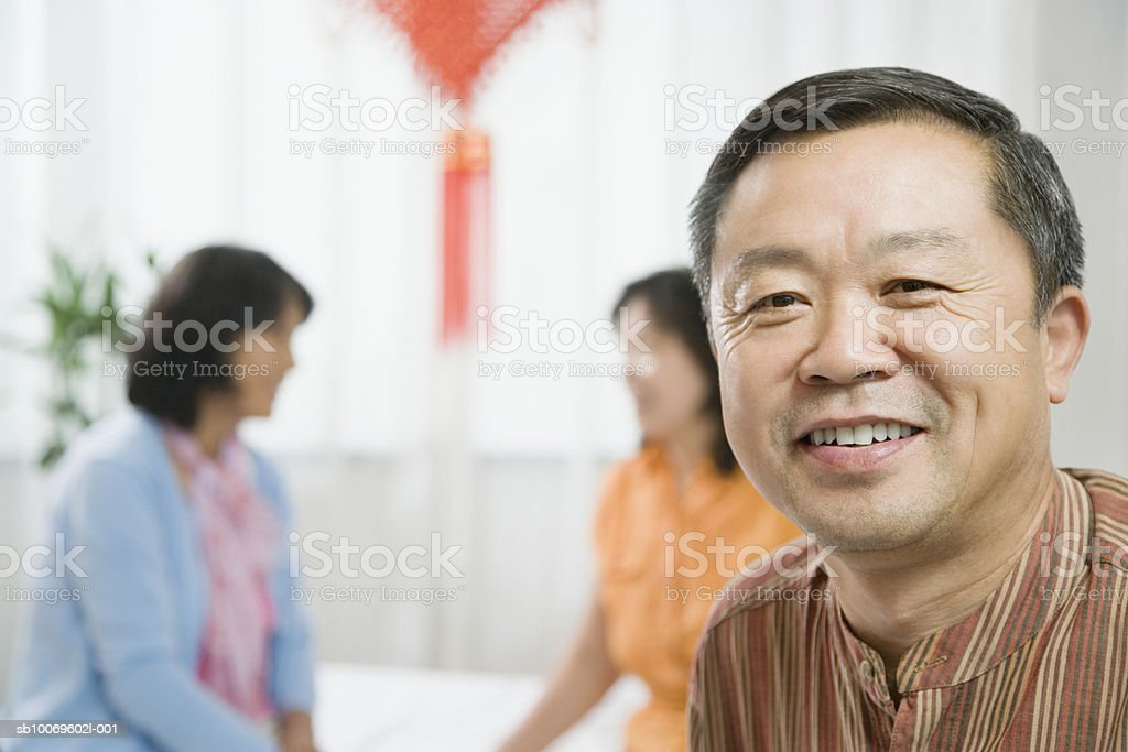 Mature man smiling, women in background foto de stock libre de derechos