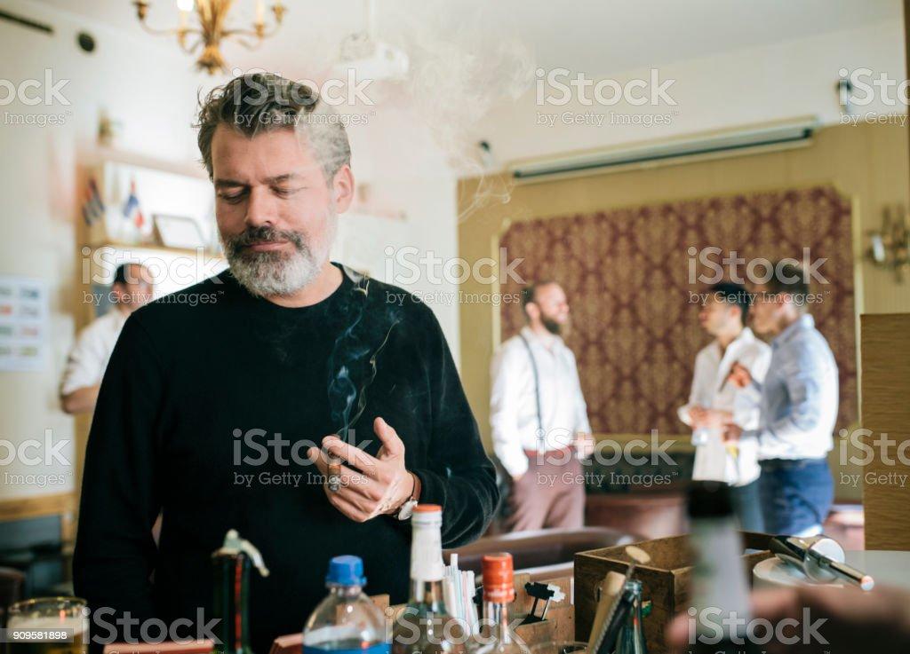 A stylish mature man ordering a drink while smoking a cigar at a...