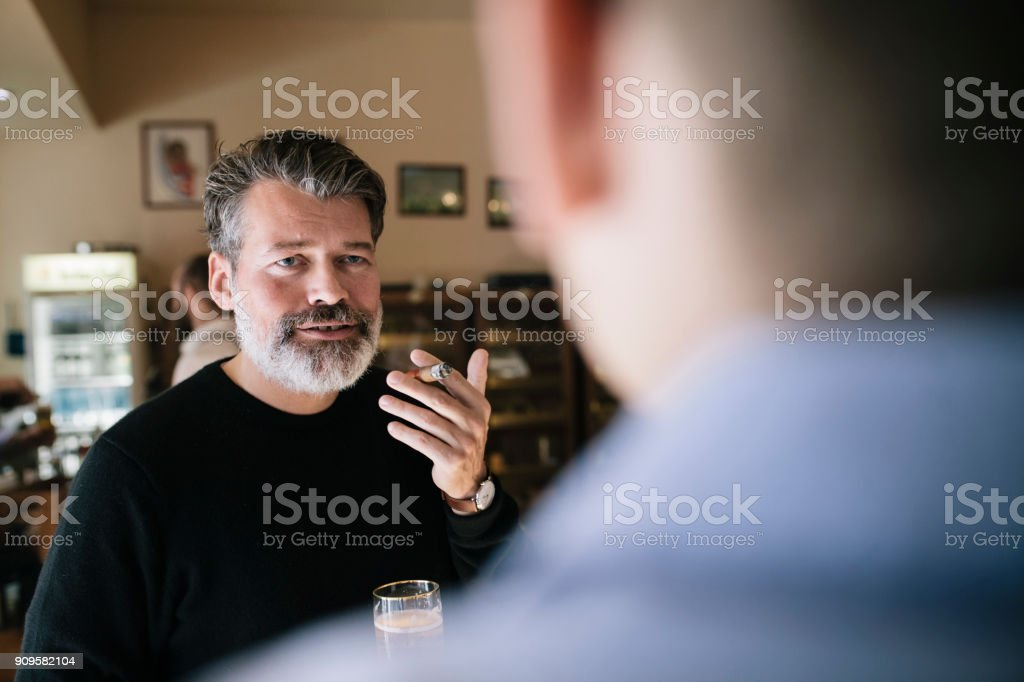 A mature man is smoking a cigar and drinking beer with his friends at...