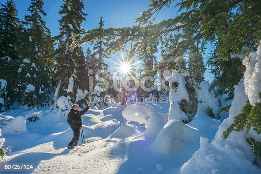 903015102 istock photo Mature Man Snowshoeing and Taking Selfie in Wilderness Forest, Canada 607257124