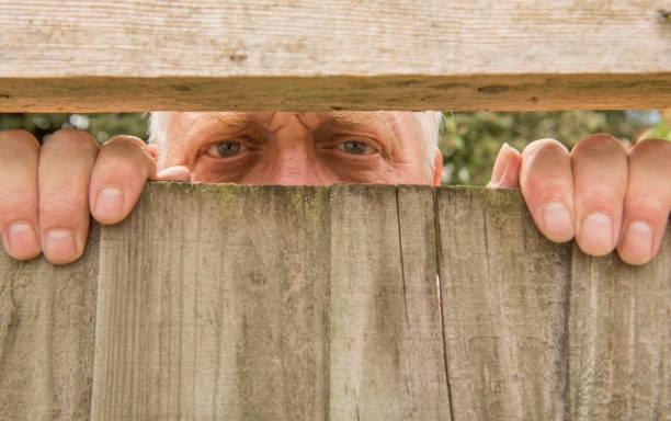 homme d'âge mûr espionnage à travers une clôture en bois - indiscret photos et images de collection