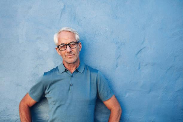 mature man standing against a blue wall - senior mann porträts stock-fotos und bilder