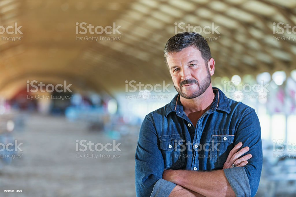 Mature man standing in barn stock photo