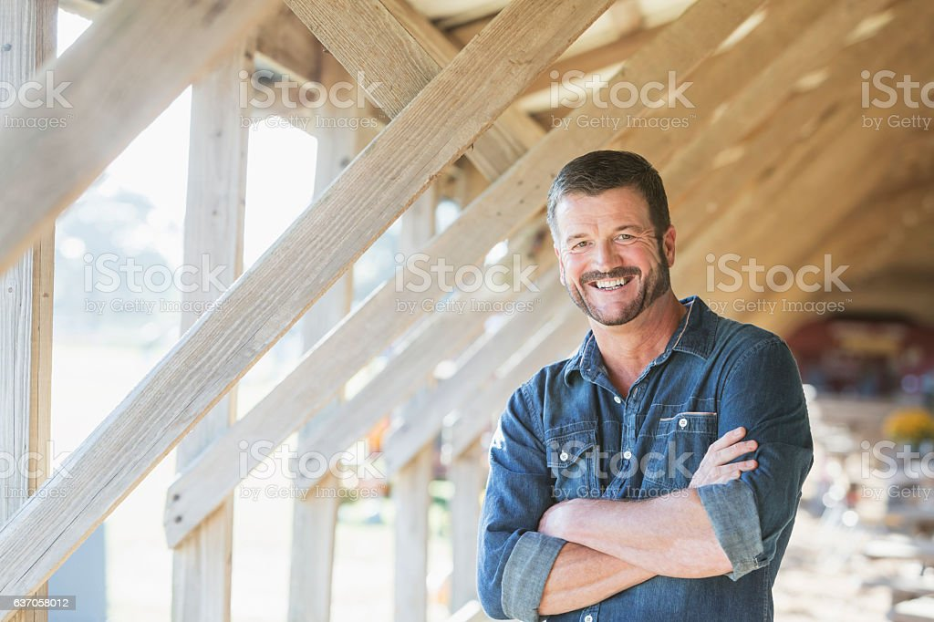 Mature man standing in barn - Photo