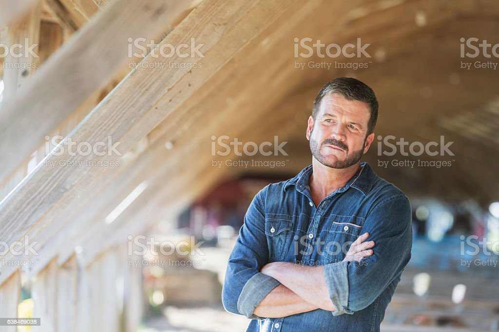 Mature man standing in barn - Photo