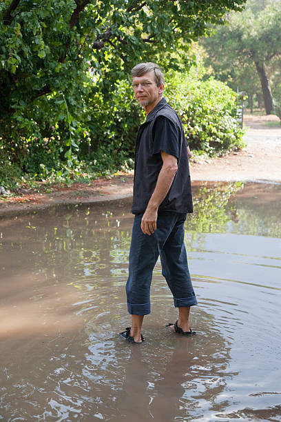 Mature Man standing in big Puddle Mature Man standing in big Puddle - Cirali, Turkey, Asia wading stock pictures, royalty-free photos & images
