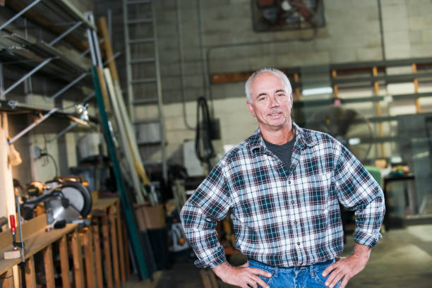 Mature man standing in factory workshop stock photo