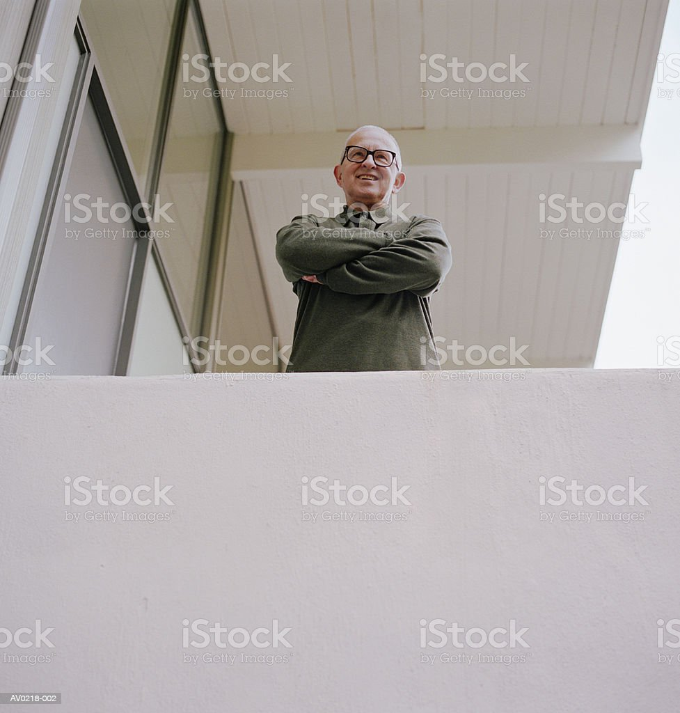 Mature man standing on balcony, low angle view 免版稅 stock photo