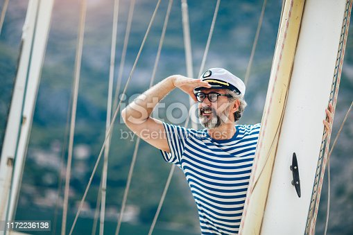 istock Mature man standing on the deck of his boat on a sunny afternoon. 1172236138