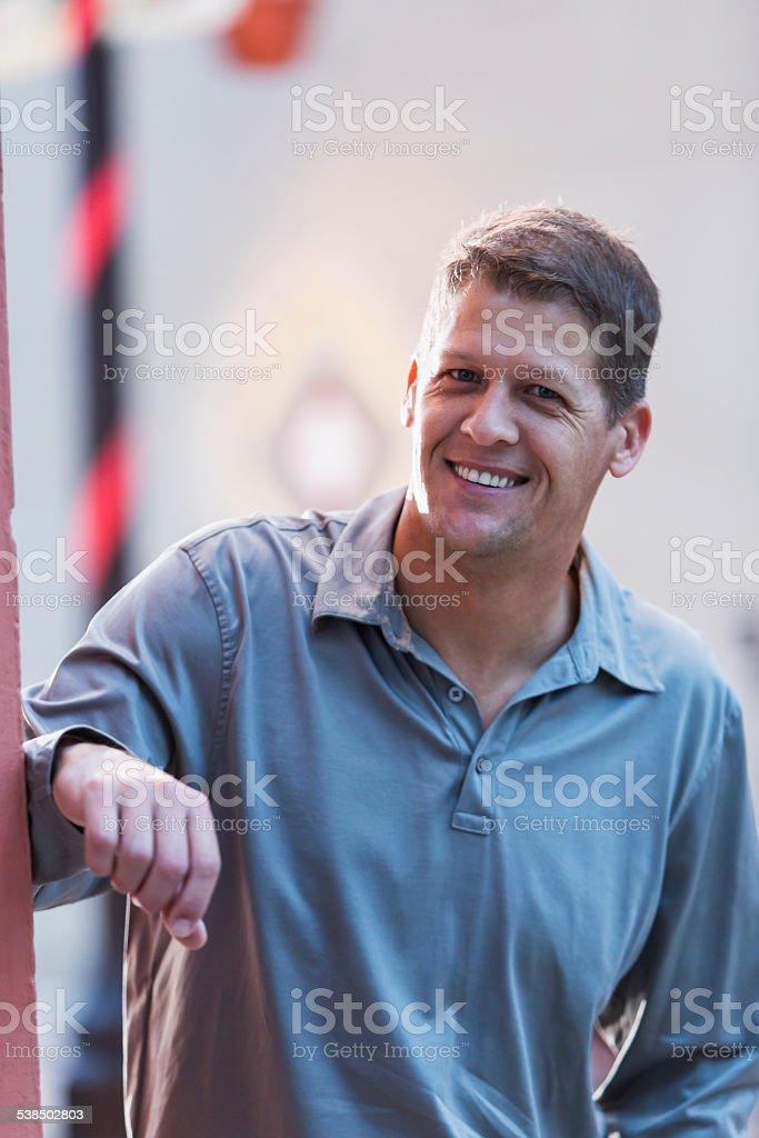 Mature man standing outdoors stock photo