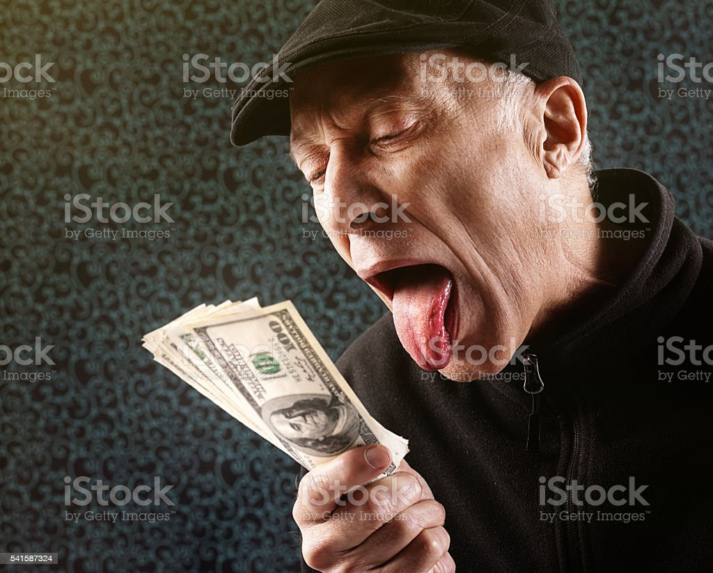 Mature man sticks tongue out by banknote bundle. Nausea? Greed? stock photo