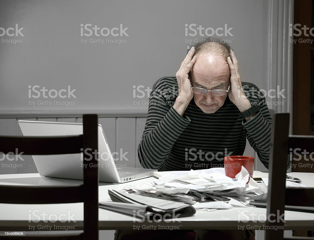 Mature man stressed out by tax preparation stock photo