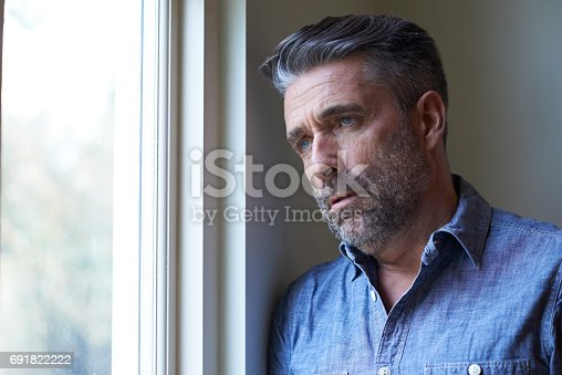 istock Mature Man Suffering From Depression Looking Out Of Window 691822222