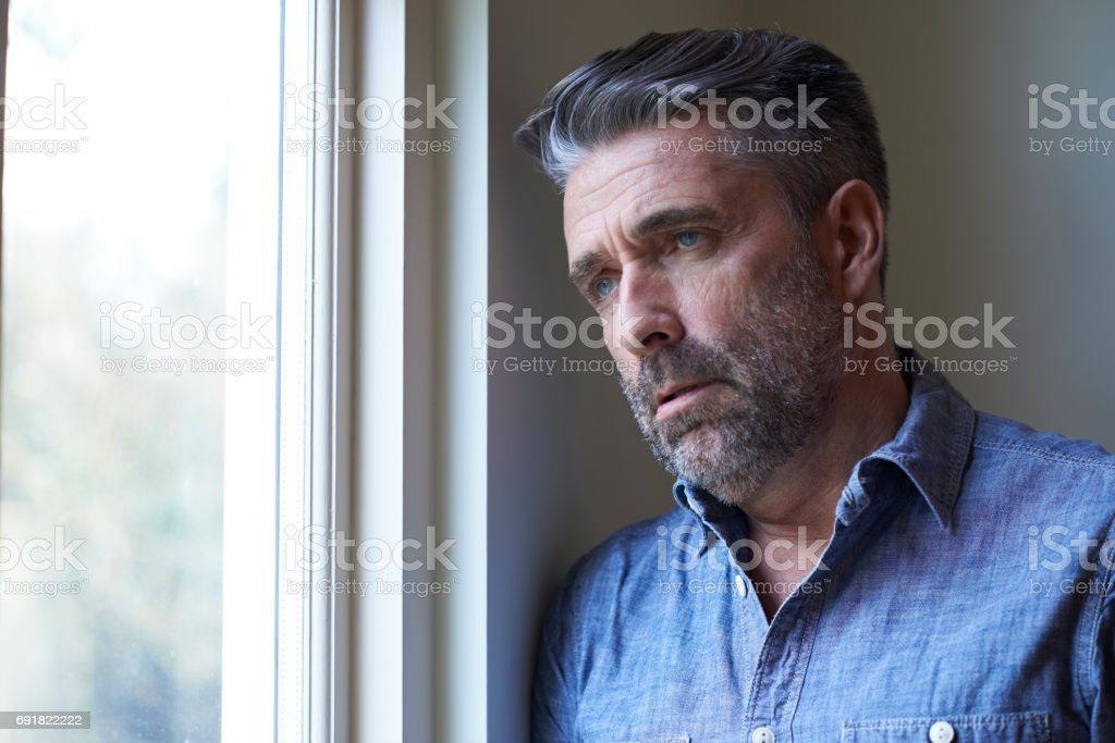 Mature Man Suffering From Depression Looking Out Of Window stock photo