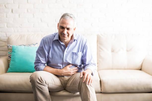 volwassen man last van buikpijn - buikpijn stockfoto's en -beelden