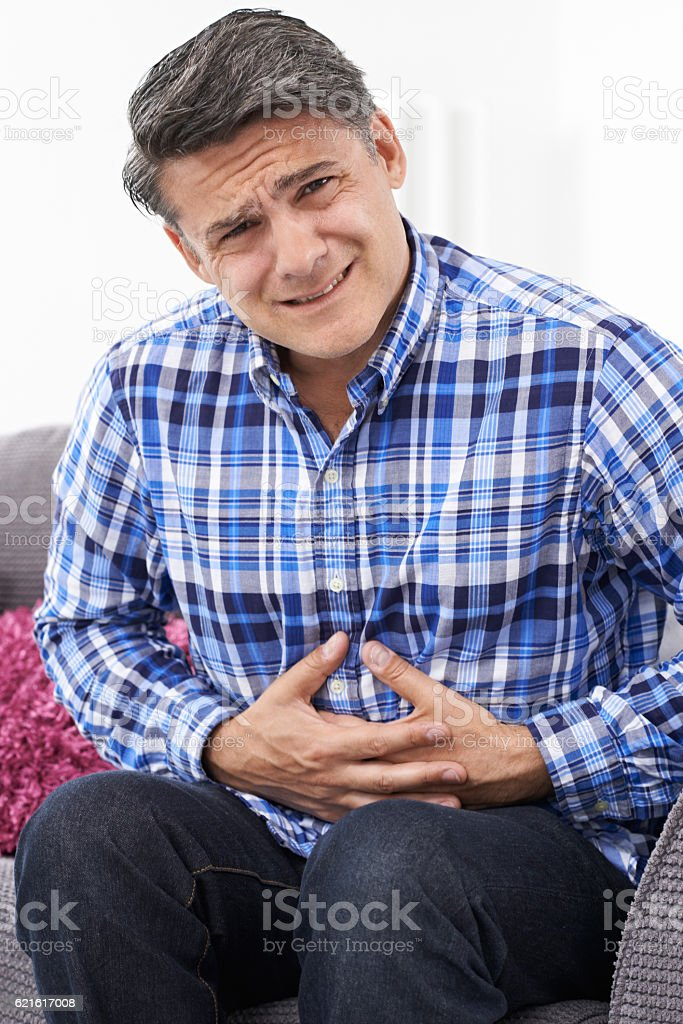 Mature Man Suffering From Stomach Pain At Home stock photo