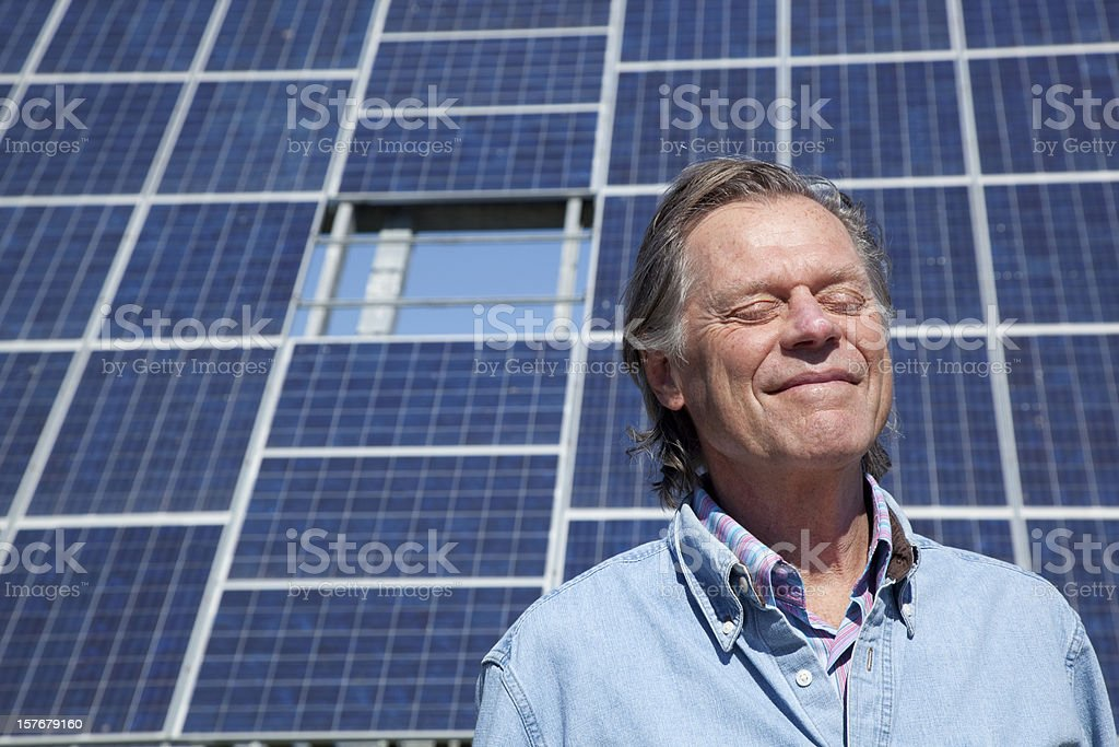 mature man suntanning in front of solar panel royalty-free stock photo