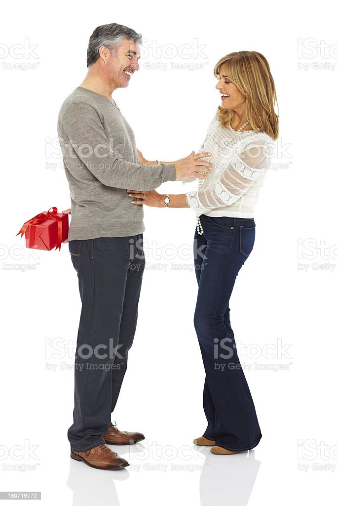 Mature man surprising his wife with gift royalty-free stock photo