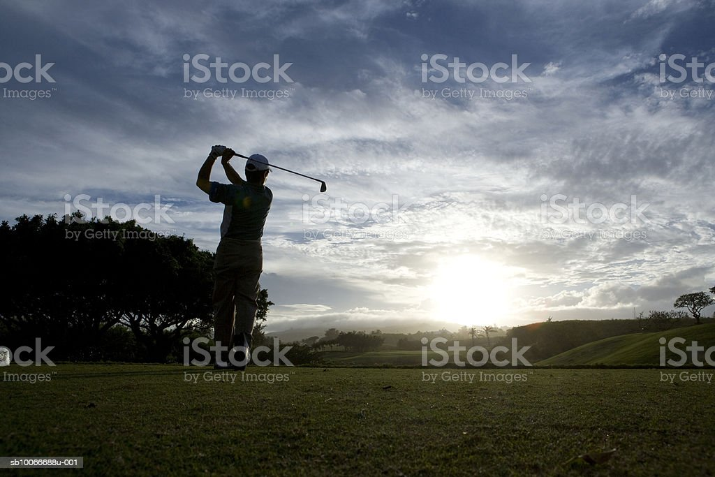 Mature man swinging golf club at dusk royalty-free stock photo