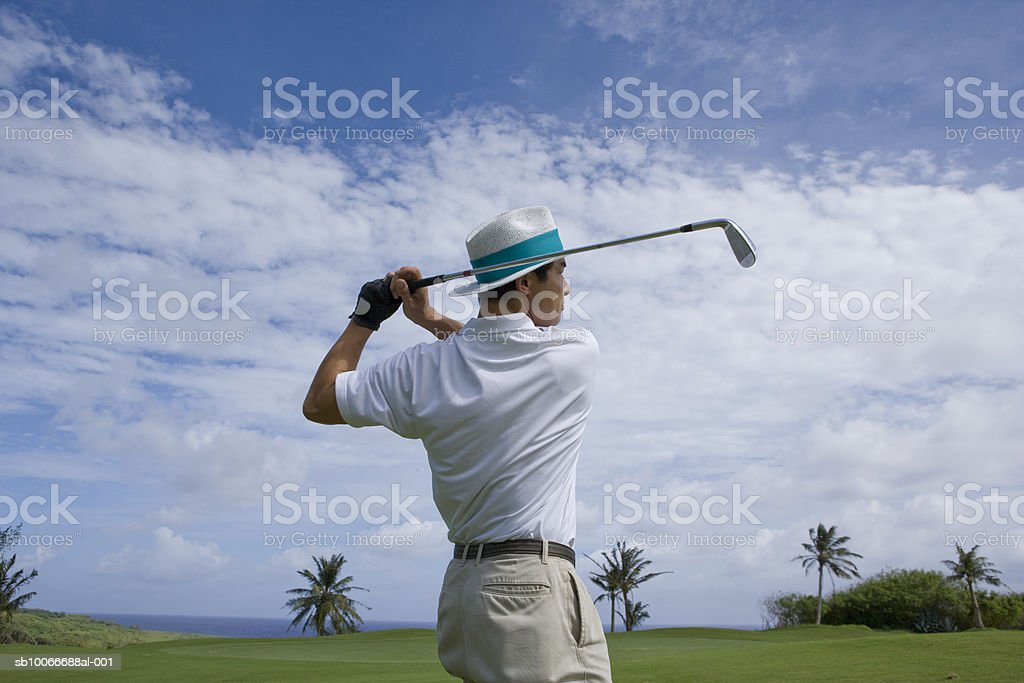 Mature man swinging golf club, looking away, side view 免版稅 stock photo