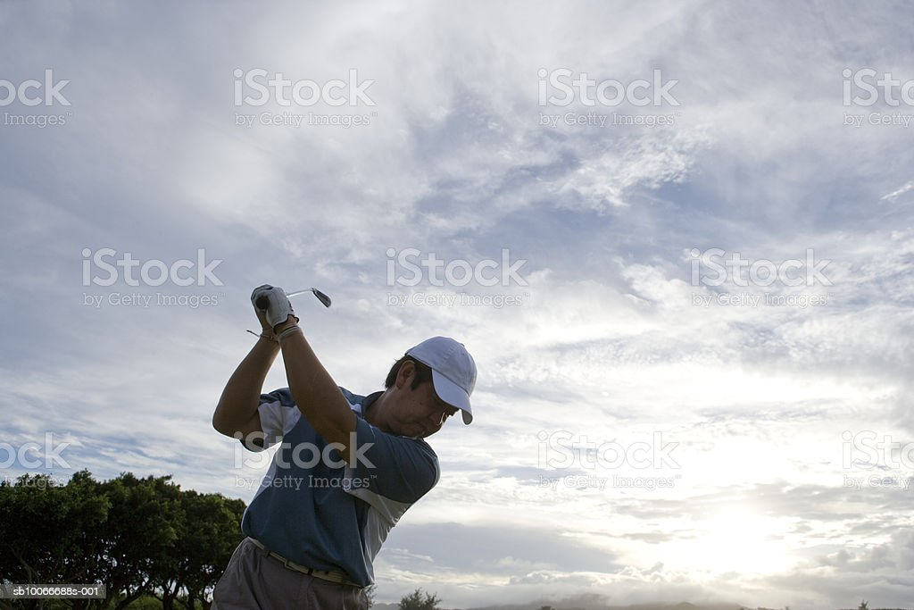 Mature man swinging golf club, low angle view royalty-free stock photo
